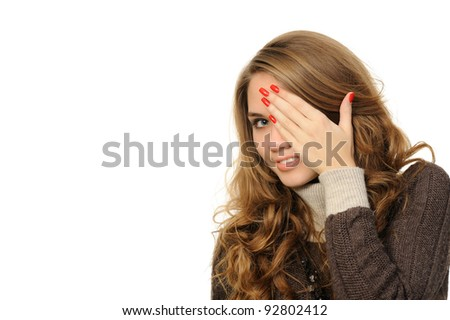Young female is gazing through her fingers - stock photo
