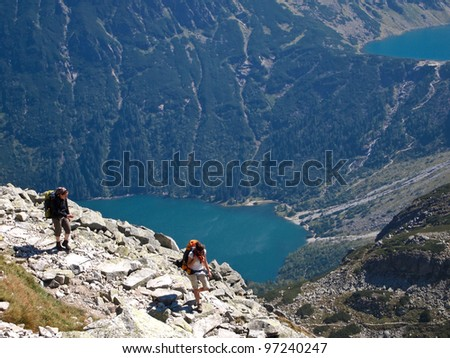 Young female is walking on footpath in mountains. - stock photo