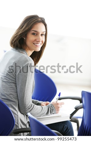 Young female is writing notes and planning her schedule - stock photo
