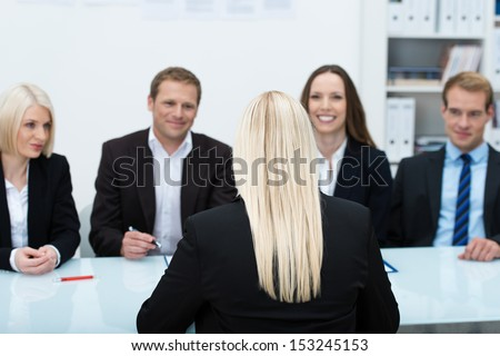 Young female job applicant in an interview sitting with her back to the camera facing a row of personnel executives - stock photo