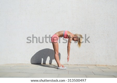 Young female jogger stretches muscles before a morning run standing against wall background with copy space area for your text message or advertising,fit woman working out outdoors in sunny summer day - stock photo