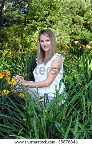 Young female kneels among the lilies at the Birmingham Botanical Garden in Birmingham, Alabama.  She is smiling and enjoying a sunny day. - stock photo