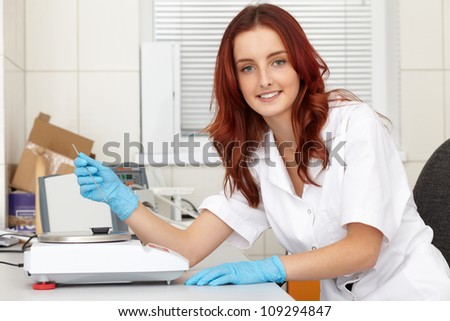 Young female lab technician works on some samples, lab shoot - stock photo