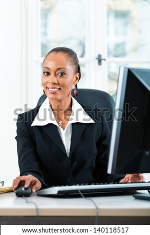 Young female lawyer or secretary working in her office on a Computer or Pc - stock photo