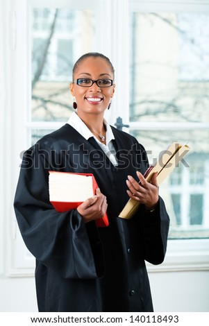 Young female lawyer working in her office with a typical law book and a file or dossier - stock photo