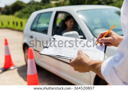 young female learner driver driving test  - stock photo