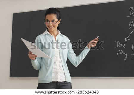 Young female lecturer holding papers and chalk against blackboard - stock photo