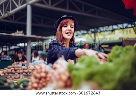 Young Female Looking For Some Vegetables At Market Place - stock photo