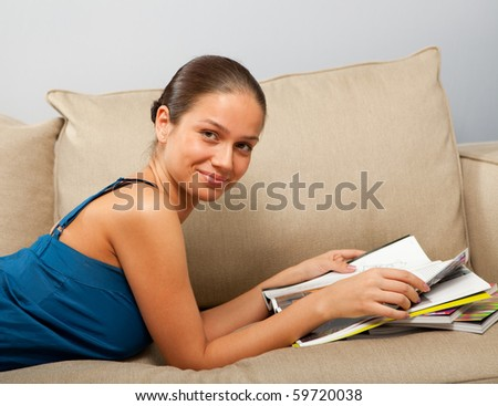 Young female lying on the sofa with magazines in hands - stock photo