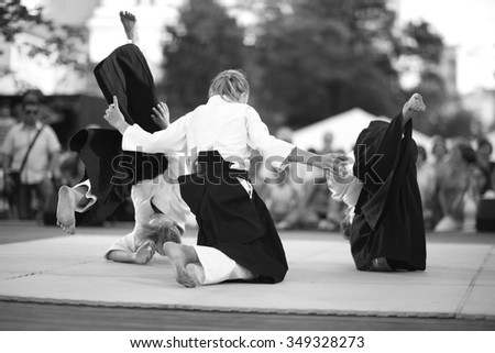 Young female master practicing aikido with two partners - stock photo
