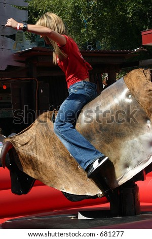 young female mechanical bull rider 2 - stock photo