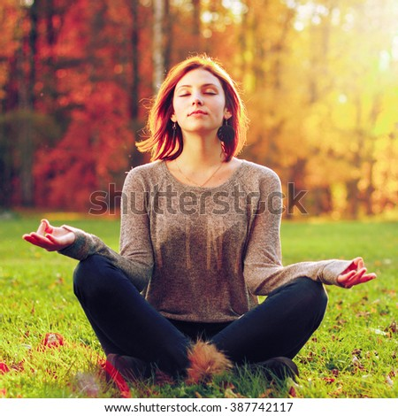 Young female meditate in park. Outdoor shot - stock photo