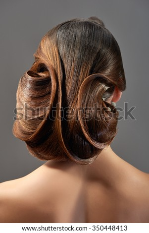Young female model with elegant evening hairstyle posing back to the camera - stock photo