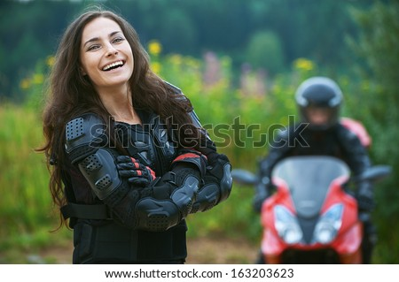 Young female motorcyclist on background of beautiful bike. - stock photo