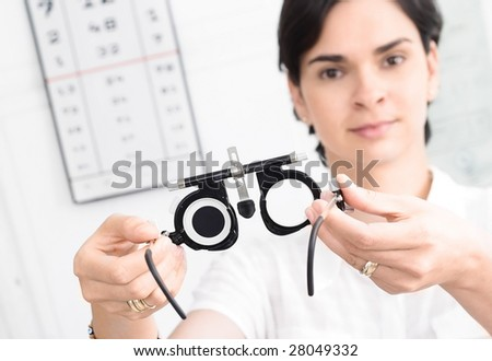Young female optometrist with an universal messbrille in hand. - stock photo