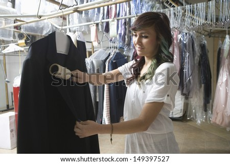 Young female owner cleaning coat with brush in laundry - stock photo