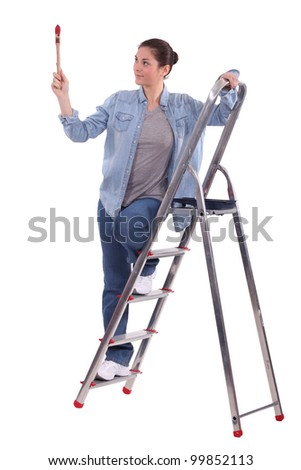 young female painter on ladder with raised brush - stock photo