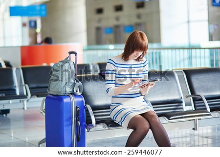 Young female passenger at the airport, using her tablet computer while waiting for her flight - stock photo
