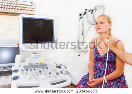 Young female patient undergoing ultrasound of thyroid gland in examination room - stock photo