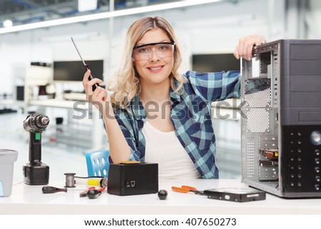 Young female PC technician posing seated at a desk in an office  - stock photo