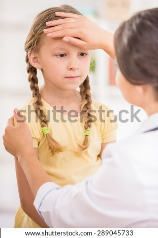 Young female pediatrician measuring temperature to her little patient. - stock photo