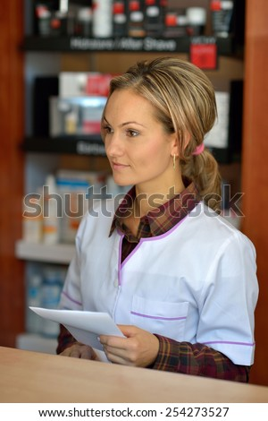 young female pharmacist holding prescription - stock photo