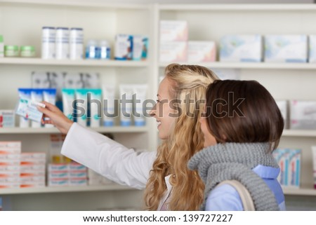 Young female pharmacist pointing at medicines in pharmacy - stock photo
