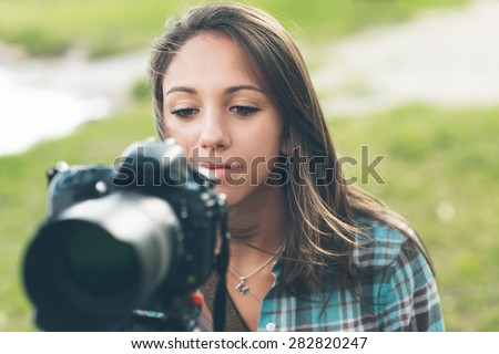 Young female photographer and videomaker shooting in a green natural setting with grass on background - stock photo