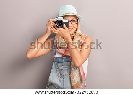 Young female photographer photographing with a retro camera and smiling - stock photo