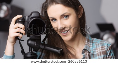 Young female photographer posing with a digital camera on tripod and lighting equipment on background - stock photo