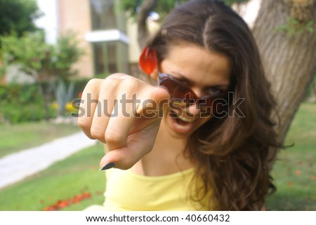 Young female pointing at you . Portrait of an attractive young woman pointing her finger. - stock photo
