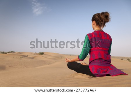 Young female practicing yoga meditation on sand dune Jaisalmer, India - stock photo