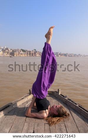Young female practising yoga pose Sarvangasana on the boat over Ganga river, India - stock photo