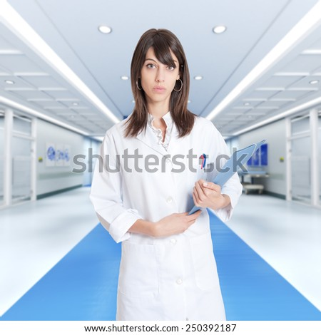 Young female professional holding a binder in a hospital corridor - stock photo