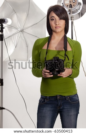 Young female professional photographer in her studio. - stock photo