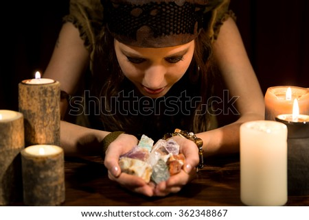 young female psychic with a lots of healing stones - stock photo
