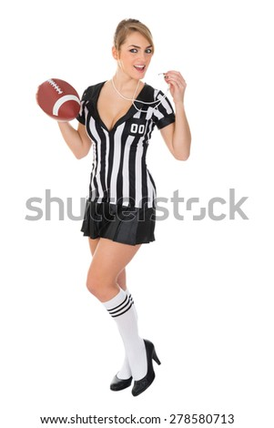 Young Female Referee Blowing Whistle With Rugby In Hand - stock photo