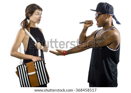 Young female refusing to be a victim of a criminal stealing her purse.  She is holding a pepper spray for self defense. - stock photo