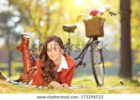 Young female relaxing on a grass with bicycle in a park - stock photo