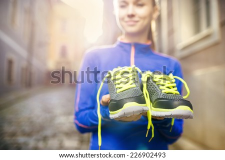 Young female runner carrying her running shoes in old city center - stock photo