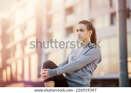 Young female runner in hoody is stretching before the run in the city street - stock photo