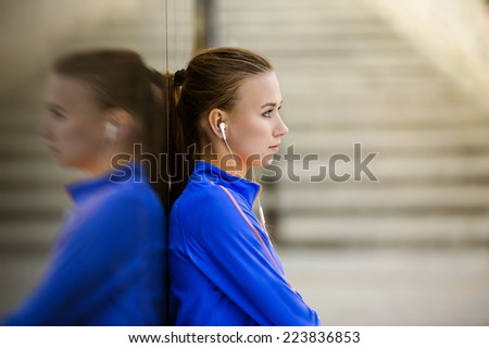 Young female runner is having break and listening to music during the run in city center - stock photo