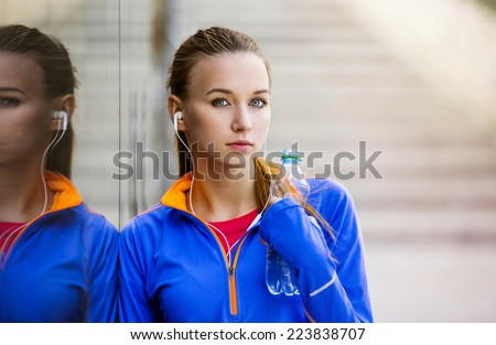 Young female runner is having break, drinking water and listening to music during the run in city center - stock photo