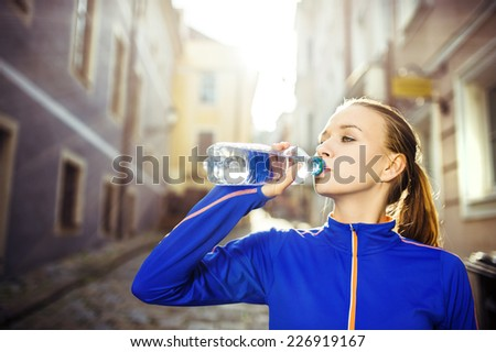 Young female runner is having break, drinking water during the run in city center - stock photo