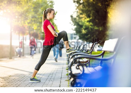 Young female runner is jogging in the city on a quay. Sport lifestyle. - stock photo
