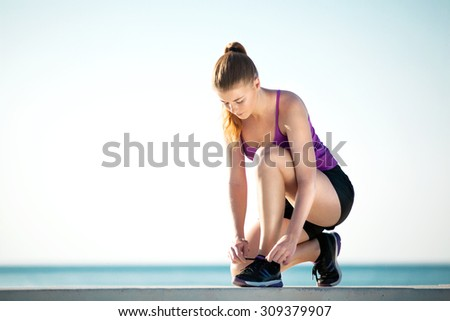 Young female runner is tying her running shoes on the ground - stock photo