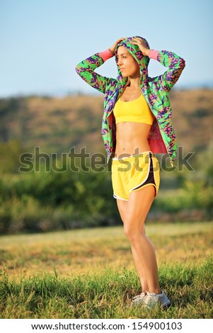 Young female runner posing in park on a sunny day - stock photo