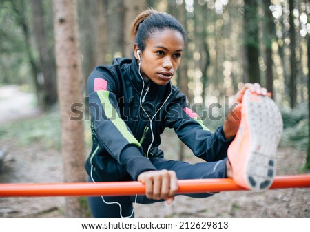 Young female runner stretching in the woods - stock photo