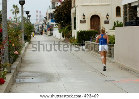 Young female running along the beach. - stock photo
