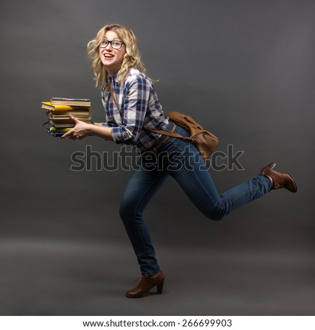 Young female running student girl rush to class with stack of books in her hands on grey background. Education or academic concept.   - stock photo